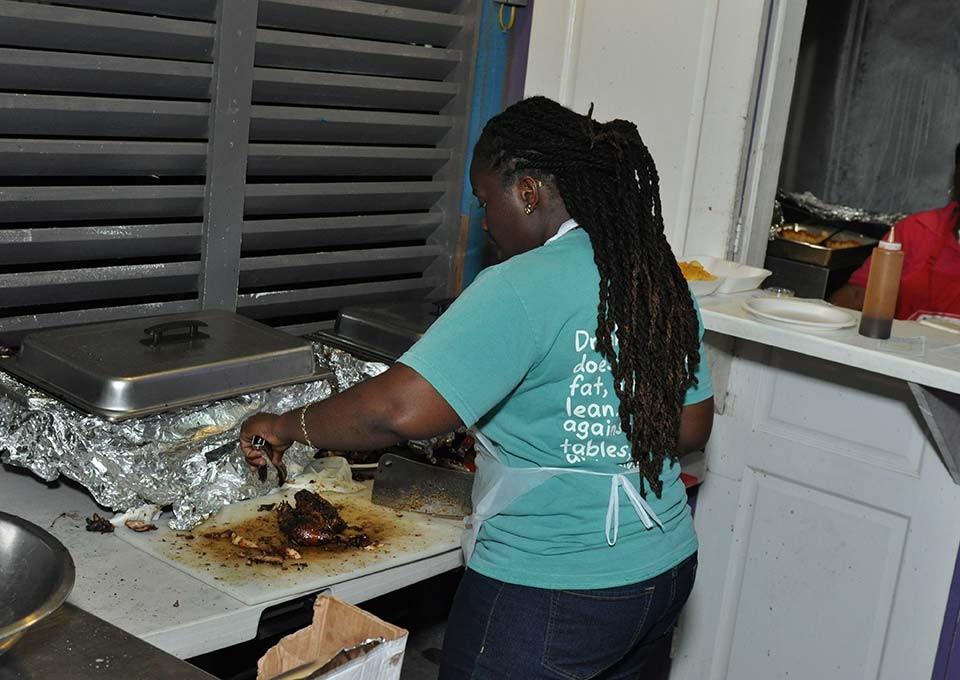 Chef chopping BBQ chicken at Island BBQ